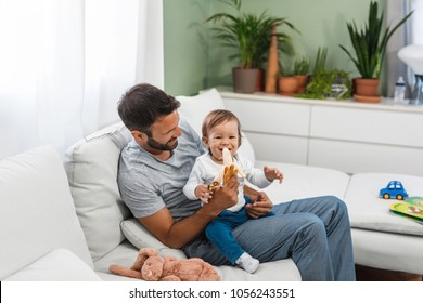 Father feeding his baby son with banana at home.