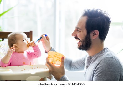 A father feeding his little baby daughter