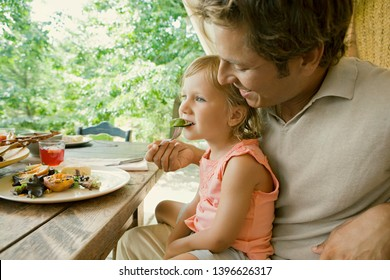 Father feeding young daughter on summer holiday villa garden, vegetables eating family, relaxing outdoors. Dad helping child girl to eat lunch on vacation break, travel leisure recreation lifestyle.