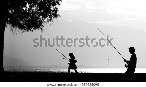 A father fishing with his daughter in the sunset. Photo taken in Port Douglas, Australia