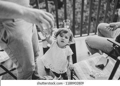 Father with friends drinks beer, child, little girl, baby takes a glass of alcohol in parents in a bar. Family spend time together in a cafe, restaurant in a summer day. Black and white photo.