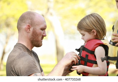 A father getting his daughter into a life jacket