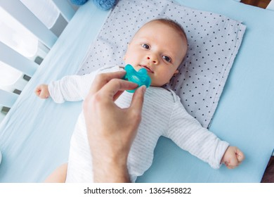 Father gives baby pacifier, baby likes it