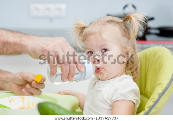 Father gives daughter drink water bottles