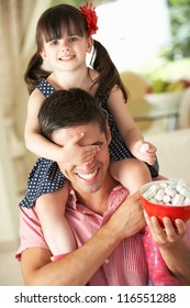 Father Giving Daughter Ride On Shoulders Indoors Whilst Eating Marshmallows