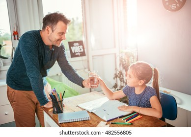 Father giving a glass of water to her daughter while she is doing homework