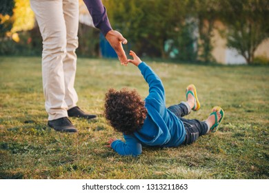 Father giving a helping hand to his son lying on the ground