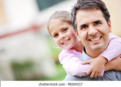 Father giving her daughter a piggyback ride