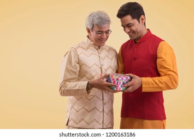 Father giving his son a gift in traditional dress