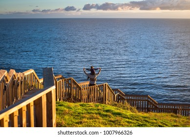 Father giving his son piggyback ride at Hallett Cove boardwalk while enjoying sunset, South Australia