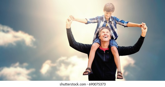 Father giving his son piggyback ride against cloudy sky with sunshine