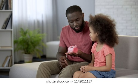 Father giving piggy bank to little daughter, teaching child to save money