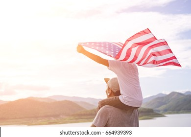 Father giving piggyback ride to his cute son with a hand held American flag in standing in the summer sunshine. USA celebrate 4th of July- Independence Day.