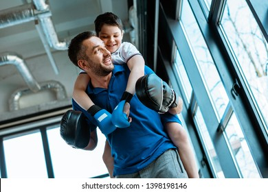 father giving piggyback ride to smiling son in boxing gloves at gym