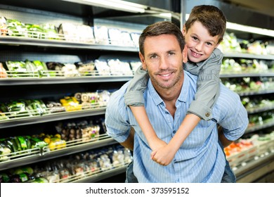 Father giving son a piggy back in grocery store