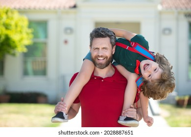 Father giving son piggyback ride after come back from school. School, family, education and outdoor concept. Funny kids face.