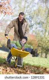 Father giving son ride in wheelbarrow through autumn leaves