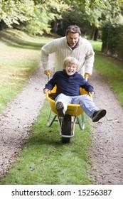 Father giving son ride in wheelbarrow through autumn woods