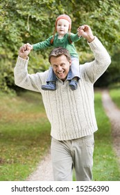 Father giving young son ride on shoulders in autumn woods