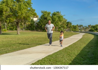 A father goes for a run with his little boy at the local park. The son keeps up with his dad during a morning workout on a sunny day.