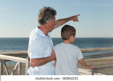 Father or grand father and his little son pointing at something with finger.
