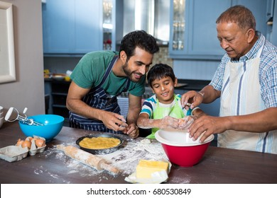 Father and grandfather looking at boy breaking egg in bowl while preparing food in kitchen at home