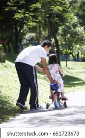 father guiding daughter to ride a bike