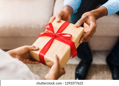 Father hands giving birthday gift to daughter, closeup