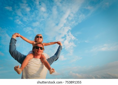 father and happy little daughter play at sky, parenting concept