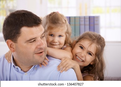 Father and happy little daughters smiling.