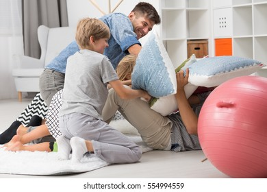 Father having a pillow fight with his children in living room