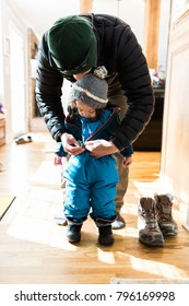 Father Helping Child, Putting on Winter Clothes for Snow Day