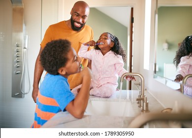 Father Helping Children To Brush Teeth In Bathroom At Home