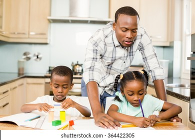 Father helping children for homework in the kitchen