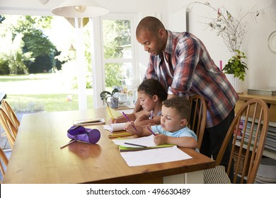 Father Helping Children With Homework At Table