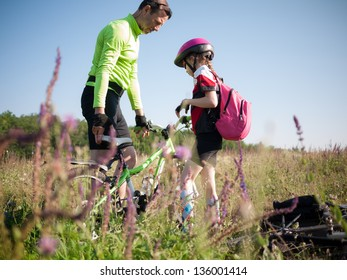 father helping daughter with her bicycle