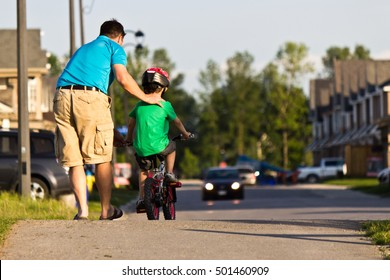 Father helping his child ride their bike