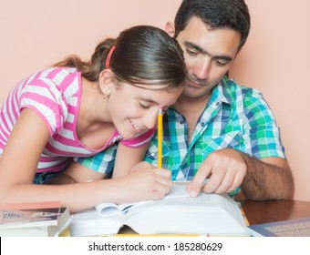 Father helping his daughter with her school homework
