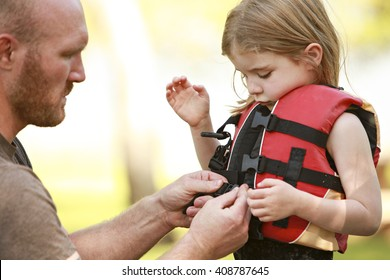 A father helping his daughter with her life jacket