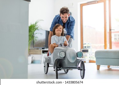 Father helping his son to drive a toy peddle car