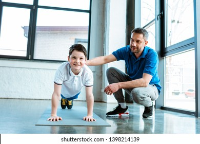 father helping smiling son with plank exercise at gym