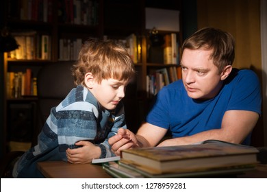 Father helping son with Homework. The father teaches the child to read