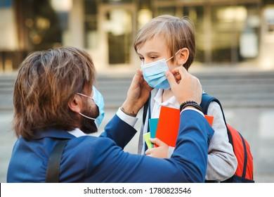 Vater hilft Sohn und auf Gesichtsschutz Maske. Kleiner Junge, der während der Koronavirus-Pandemie zur Schule geht. Geschäftsmann, Vater und Sohn gehen zur Schule. Der Schuljunge ist bereit, zur Schule zu gehen.