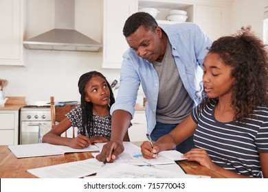Father Helping Two Daughters Sitting At Table Doing Homework