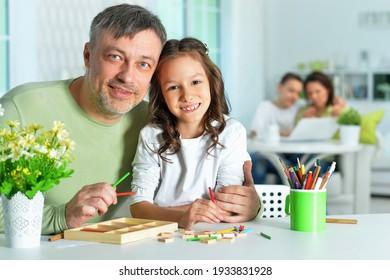 Vater hilft seiner süßen kleinen Tochter bei ihren Hausaufgaben