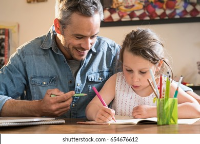 A father helps his little daughter to do her homework for the school.