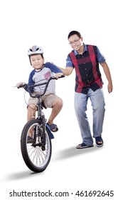 Father helps his son to ride a bike while holding the bike, isolated on white background