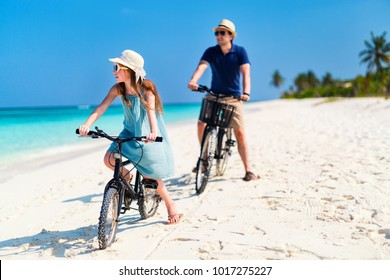 Father and her little daughter riding bikes at tropical beach having fun together
