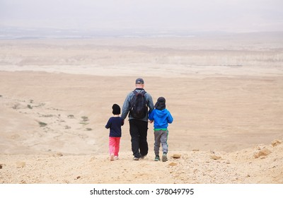 father hiking with two kids in the desert