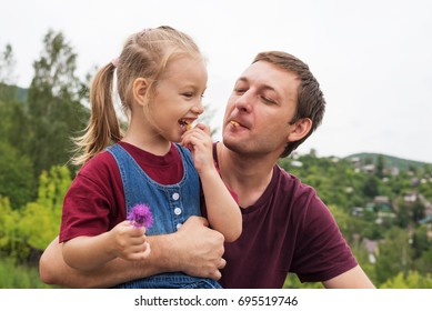 Father and his 4-year-old daughter on a hill on a summer day eating little cookies.